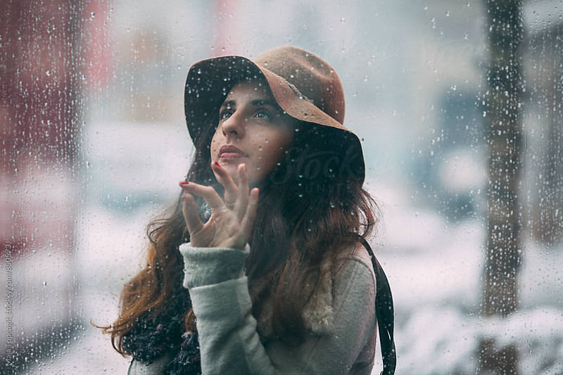 Woman looking through window covered with raindrops by Maja Topcagic for Stocksy United