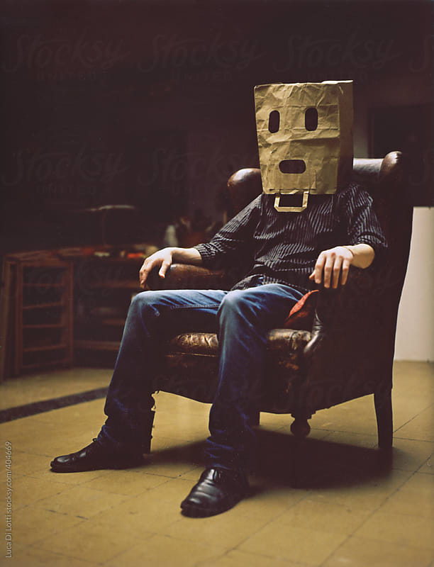 A man sitting on a armchair wearing a spooky paper-bag as a mask. by Luca Di Lotti for Stocksy United