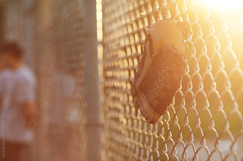 Baseball Glove hanging of Fence during summer game. by Nick Wong for Stocksy United