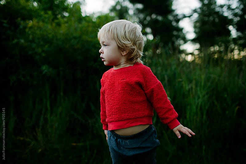 Small, alert child listens and watches while standing in nature. by Julia Forsman for Stocksy United