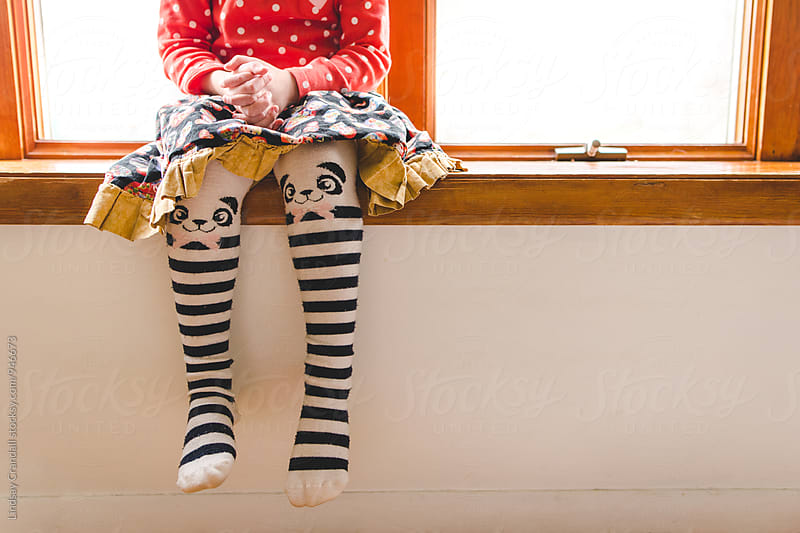 Young child sitting on window wearing cute tights by Lindsay Crandall for Stocksy United