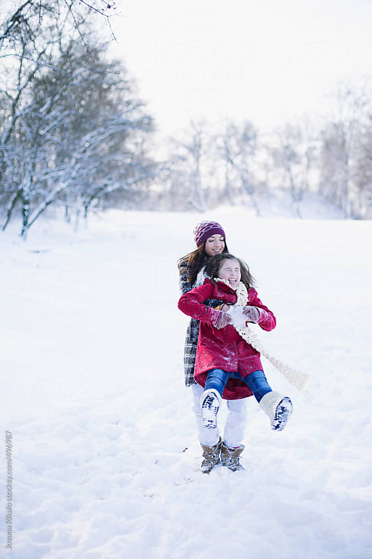 Two happy sisters playing in the snow by Jovana Rikalo for Stocksy United