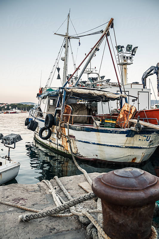 old dirty fishing boat in the harbour by Leander Nardin for Stocksy United