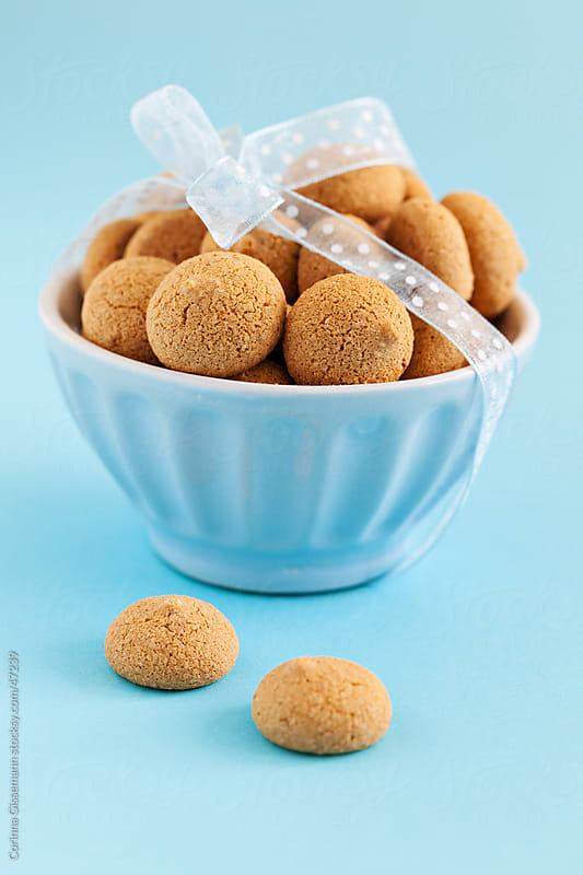 a group of amaretti cookies in a blue bowl with ribbon on blue background by Corinna Gissemann for Stocksy United