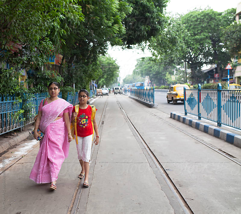 Mother and daughter walking trough city area by PARTHA PAL for Stocksy United