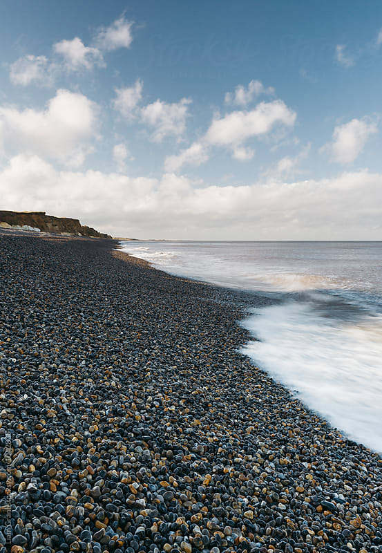 Crashing waves and pebble beach below a blue sky. Norfolk, UK. by Liam Grant for Stocksy United