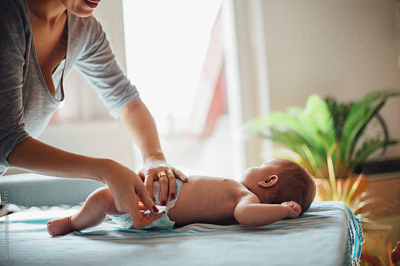Mom Giving Baby a Diaper Change  by Lumina for Stocksy United