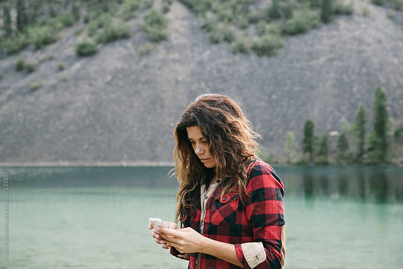 woman texting in front of a lake by Shaun Robinson for Stocksy United
