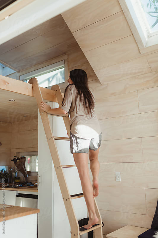 Young woman climbing ladder in tiny home. by Kate Daigneault for Stocksy United