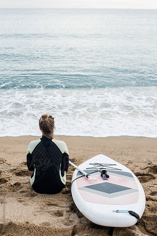 Blonde girl with her paddle looking at the sea by Bisual Studio for Stocksy United