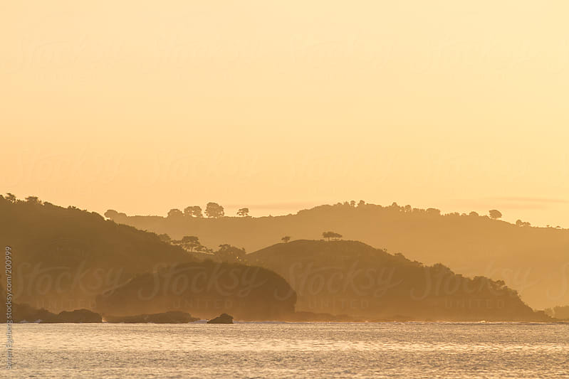Golden sunset landscape  on rocky coastline with ocean in forground by Soren Egeberg for Stocksy United