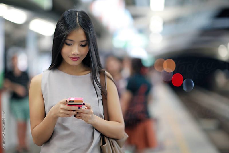 Asian Woman Texting at the Underground Station by Lumina for Stocksy United