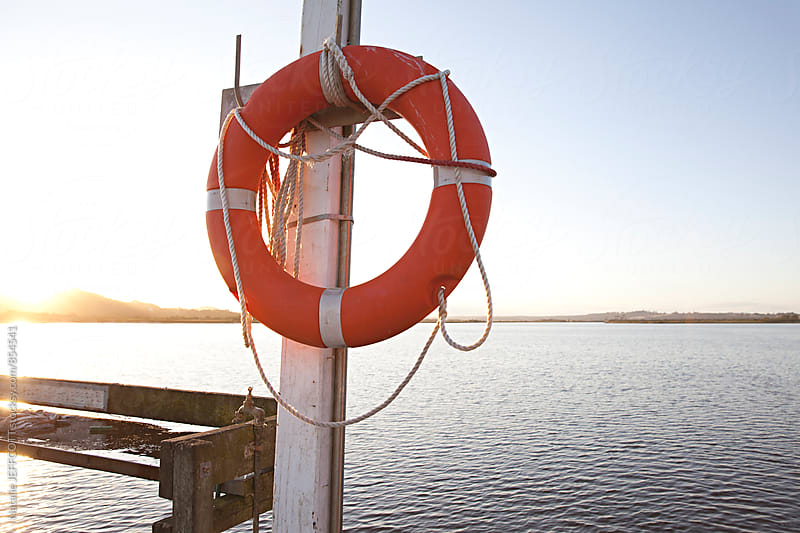 The pier at Marlo, Australia with life buoy at sunset by Natalie JEFFCOTT for Stocksy United