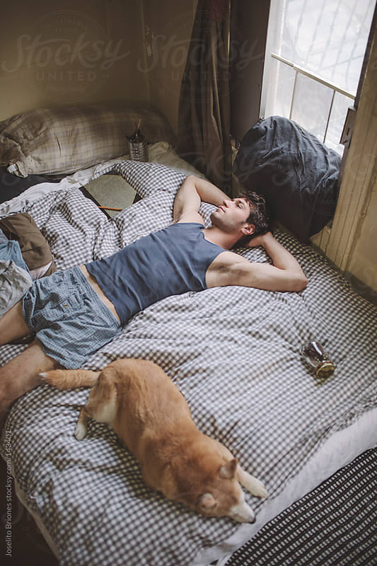 Man Resting in Bed at Home with Dog by Joselito Briones for Stocksy United