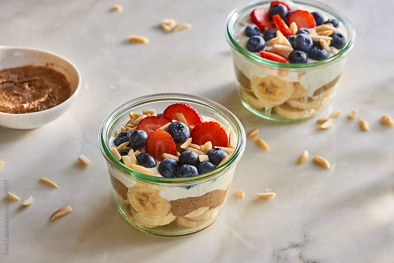 Almond butter and berries breakfast bowls with banana and yogurt by Trent Lanz for Stocksy United