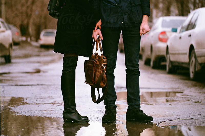A couple on puddle road by Danil Nevsky for Stocksy United