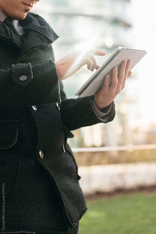 Young businessman using digital tablet by Davide Illini for Stocksy United