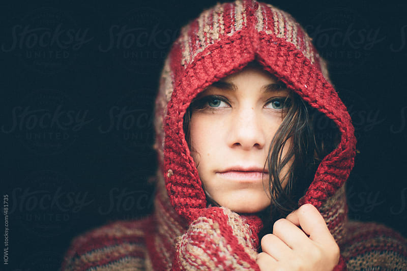 Portrait of a woman in hooded sweater by HOWL for Stocksy United