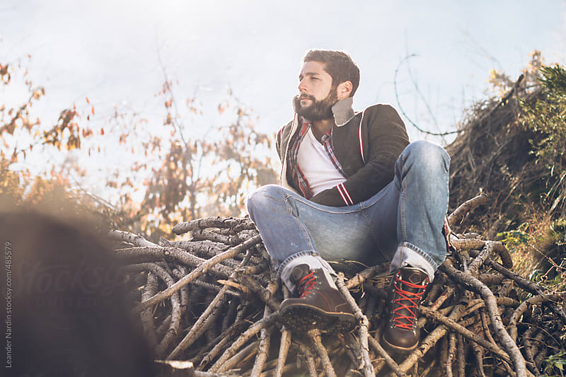 young bearded man lying on woodpile by Leander Nardin for Stocksy United
