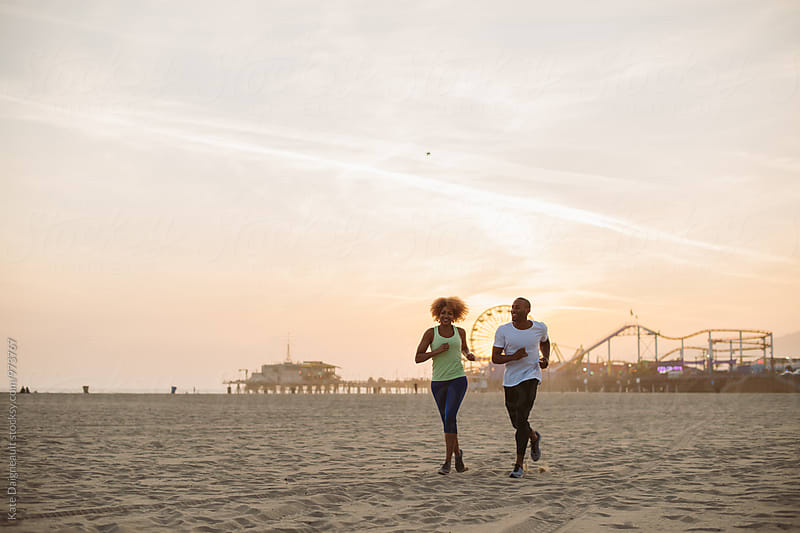 Youn African American couple running on the beach at sunset together. by Kate Daigneault for Stocksy United
