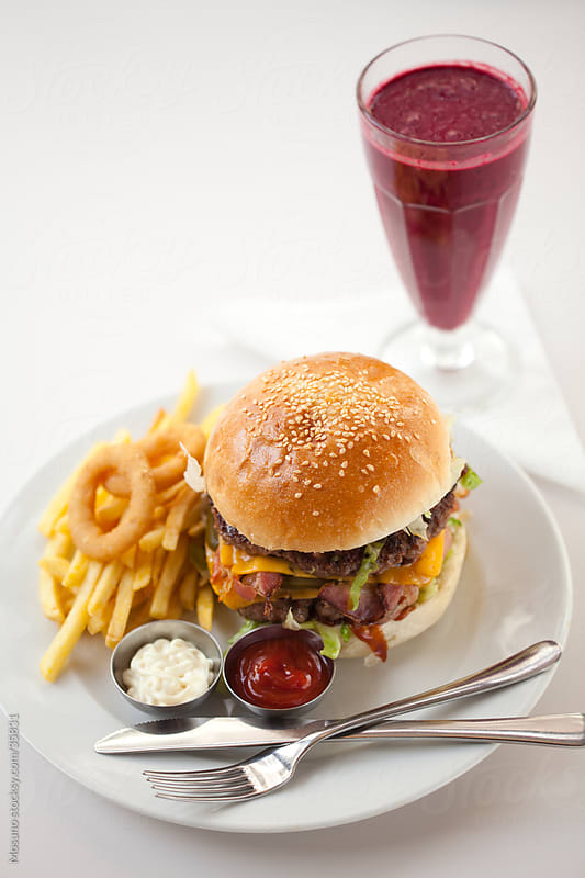 Hamburger and fruit smoothie served in a restaurant. by Mosuno for Stocksy United