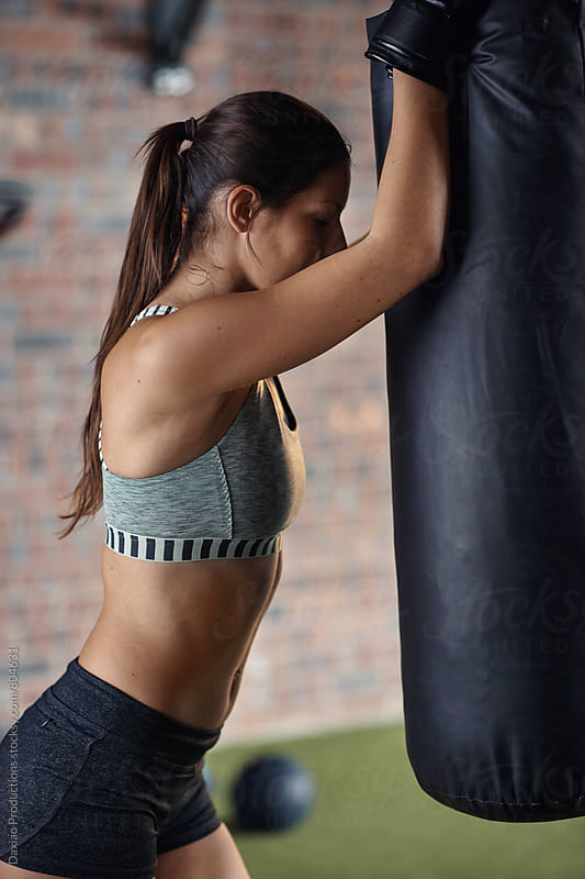 fit healthy woman resting on punching bag during boxing training by Daxiao Productions for Stocksy United