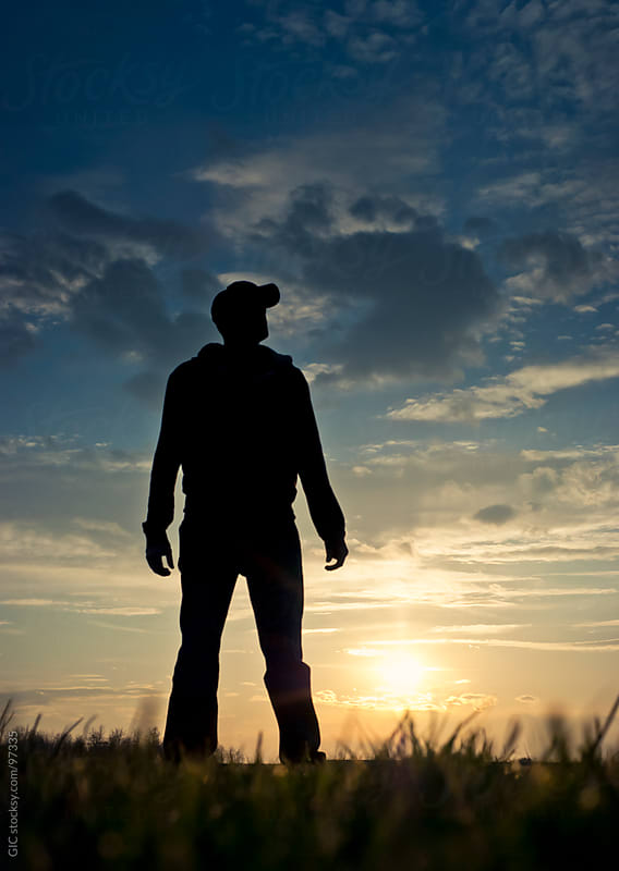Silhouette of Man Standing in a Field at Sunset by GIC for Stocksy United
