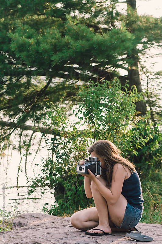 teen girl taking photograph with vintage instant camera by Deirdre Malfatto for Stocksy United