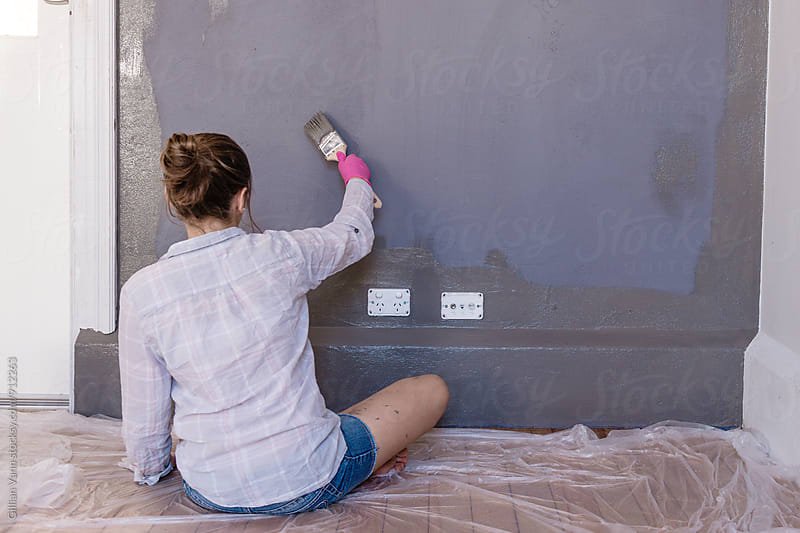 teen girl painting a wall in a dark grey colour by Gillian Vann for Stocksy United