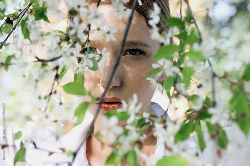 Beautiful spring portrait of a young woman i white flowers by Hamza Kulenović for Stocksy United