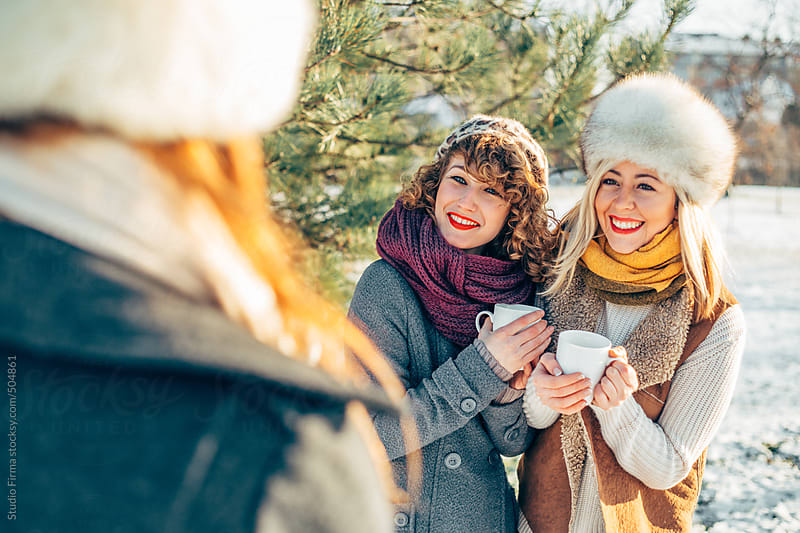 Girlfriends drinking coffee outside. by Studio Firma for Stocksy United
