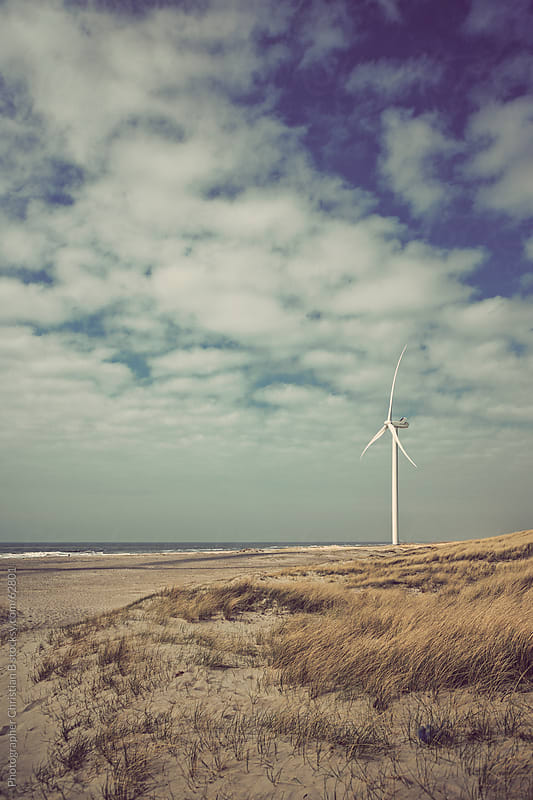 Wind turbine at shore line by Photographer Christian B for Stocksy United