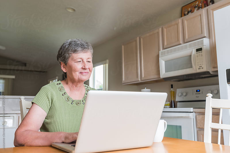 Woman Smiles and Uses Computer by suzanne clements for Stocksy United