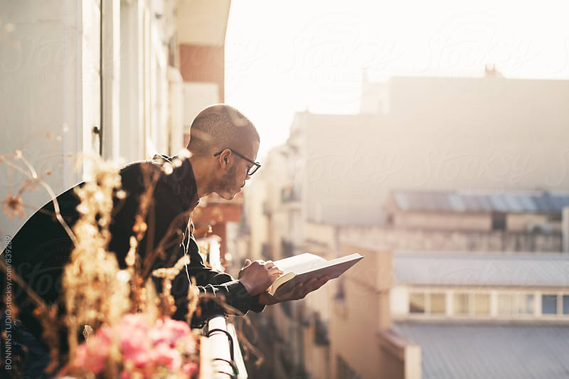 Latin man in the balcony reading a book at sunrise. by BONNINSTUDIO for Stocksy United