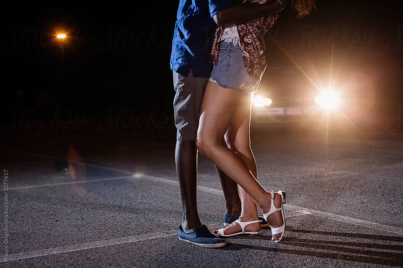 Couple kissing on street at night by Mauro Grigollo for Stocksy United