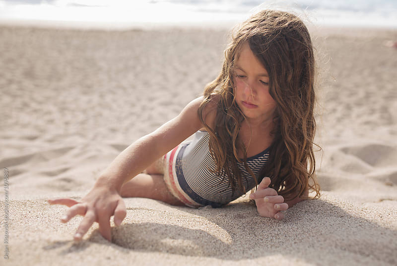 Girl playing in the sand. by Dejan Ristovski for Stocksy United