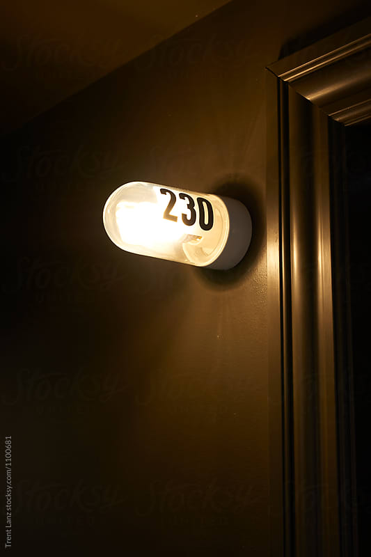 230 lamp sign on brown wall by Trent Lanz for Stocksy United