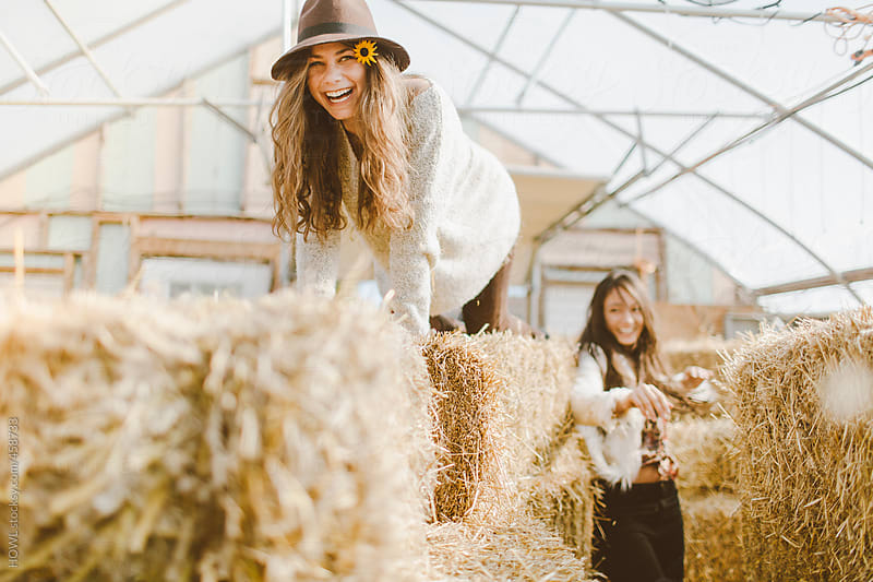 Girl climbs on hay stacks in farm's greenhouse  by HOWL for Stocksy United