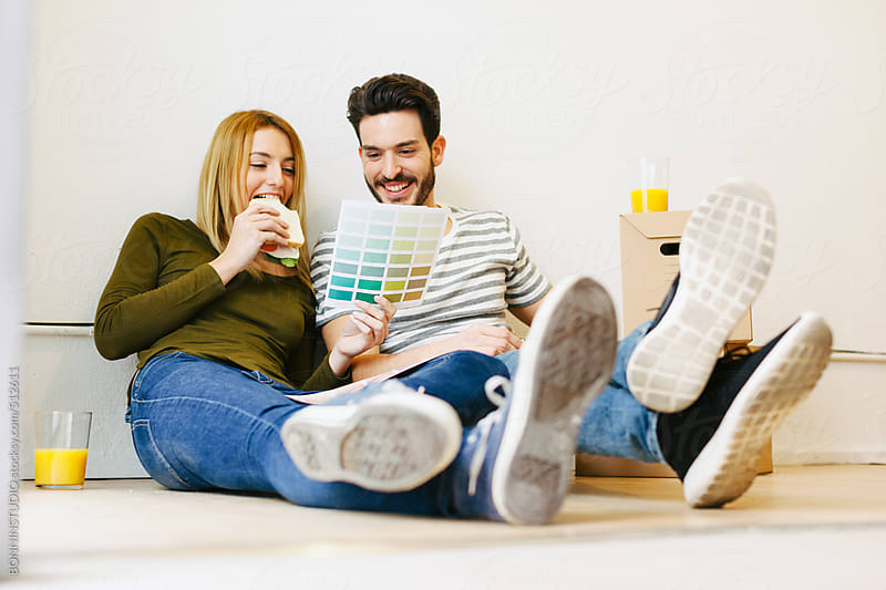 Young couple eating a sandwich while looking at swatch colours for the new home.  by BONNINSTUDIO for Stocksy United
