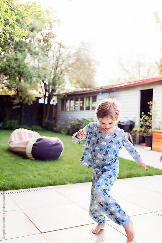 Happy boy in pajamas dancing in a yard in the evening by Angela Lumsden for Stocksy United