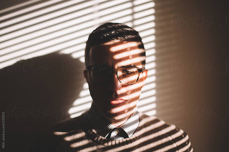 Elegant Man With Glasses Close to a Window . Portrait by HEX. for Stocksy United