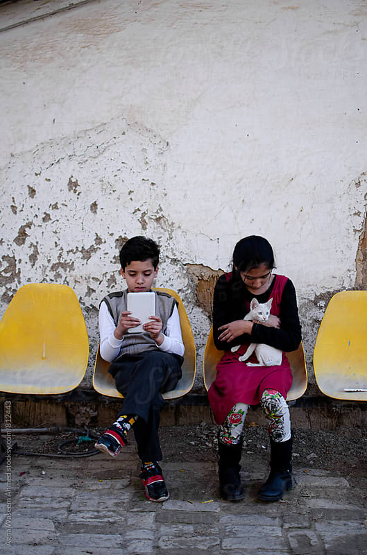 Two children , one holding a white kitten the other one working on his tablet ! by Agha Waseem Ahmed for Stocksy United