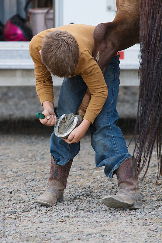 child cleans horse's hoof by Tana Teel for Stocksy United