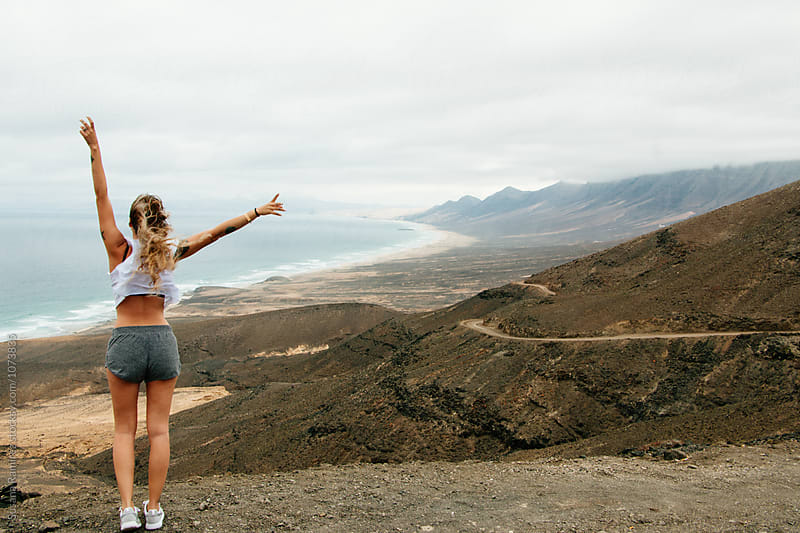Woman raising arms with incredible landscape of mountains and beach by Susana Ramírez for Stocksy United