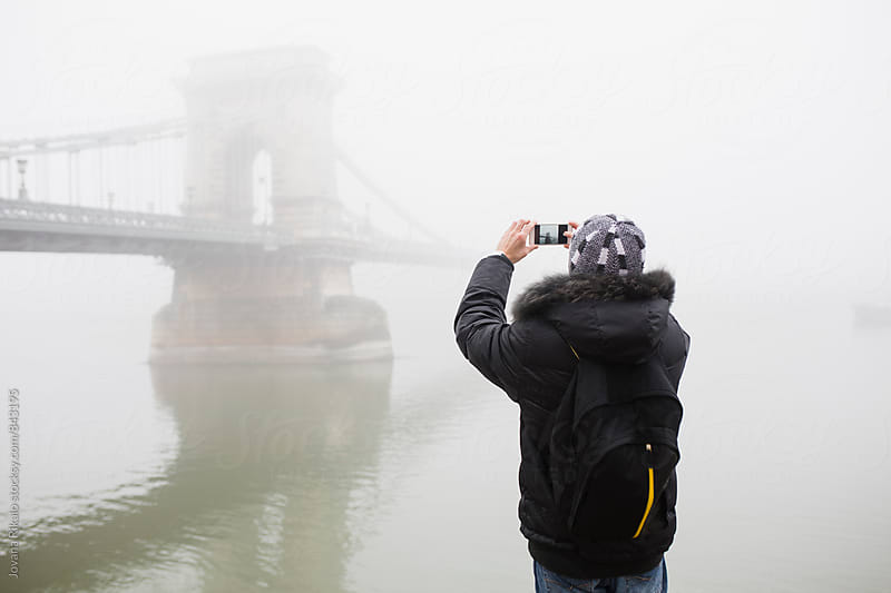 Man taking photos of a Chain Bridge by Jovana Rikalo for Stocksy United