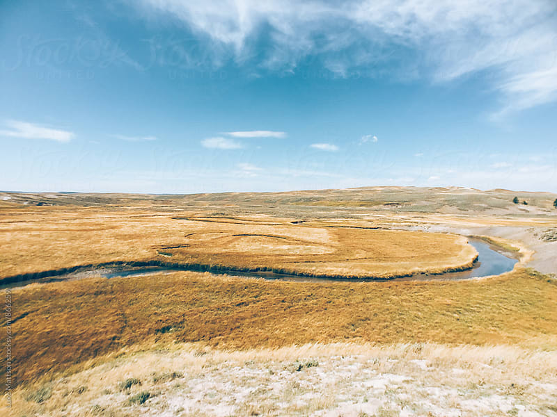 Calm River Winding Through Open Plains by Luke Mattson for Stocksy United