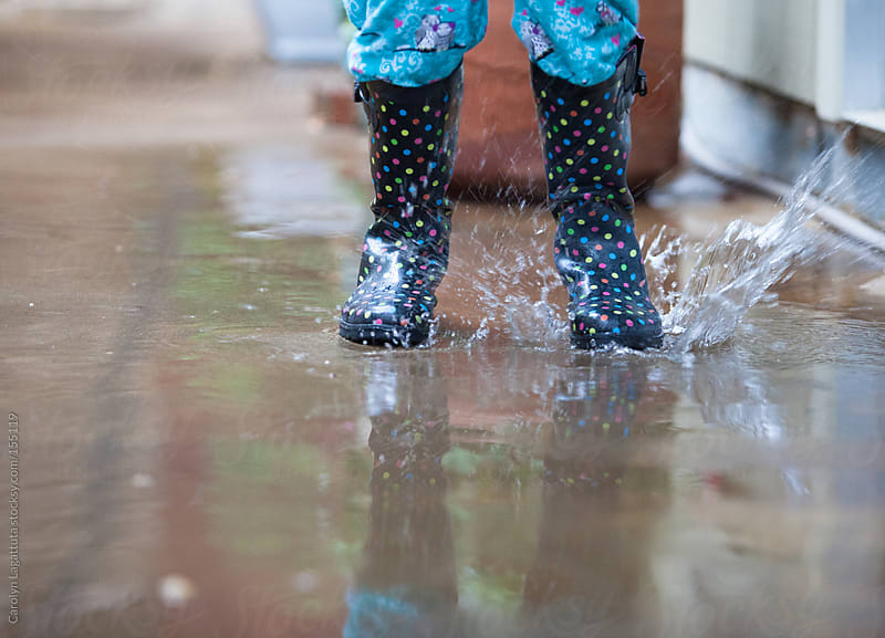 Young girl jumping in rain puddles by Carolyn Lagattuta for Stocksy United