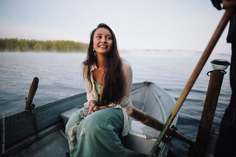 Beautiful native American girl waits patiently on her row boat  by HOWL for Stocksy United