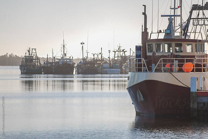 Fishing trawlers moored together in harbour by Ben Ryan for Stocksy United