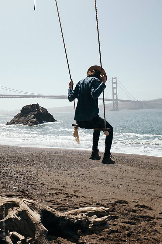 Swinging on the beach. by Lucas Saugen for Stocksy United